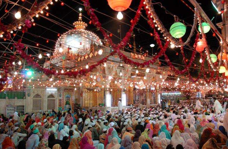 crowded ajmer sharif dargah at night decorated with colourful lights