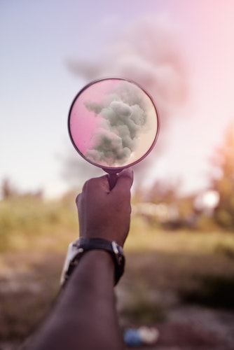 man's hand holding a magnifying glass to focus on smoke rising from a distance