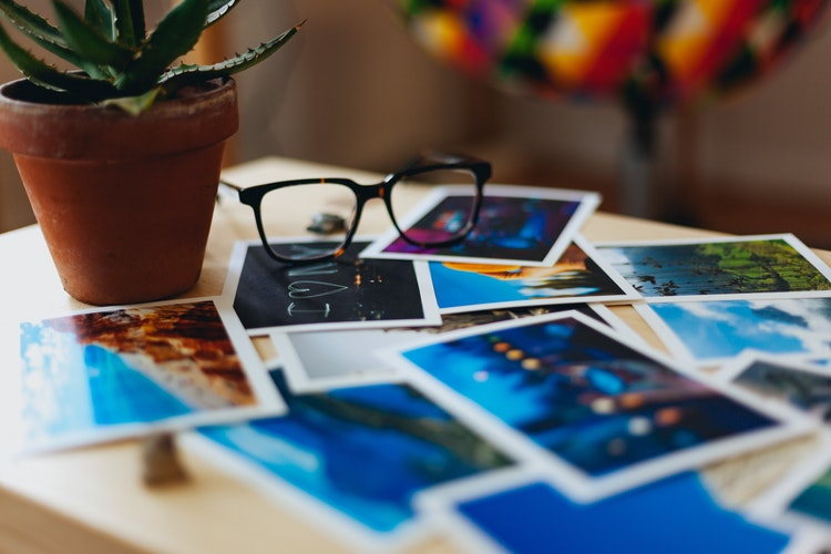 pile of travelling photos lying on a table beside a potted plant and a pair of glasses
